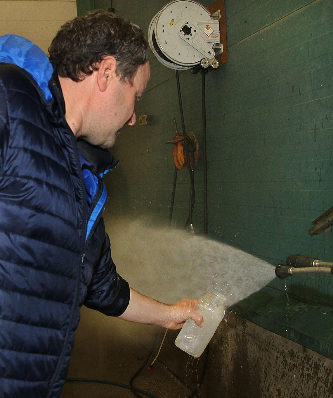 Bjørnar Skjemstad tar prøver av vann fra vaskehall.