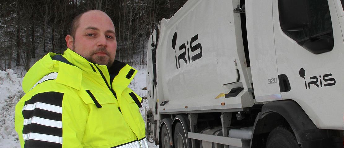 Mann ved avfallsbil