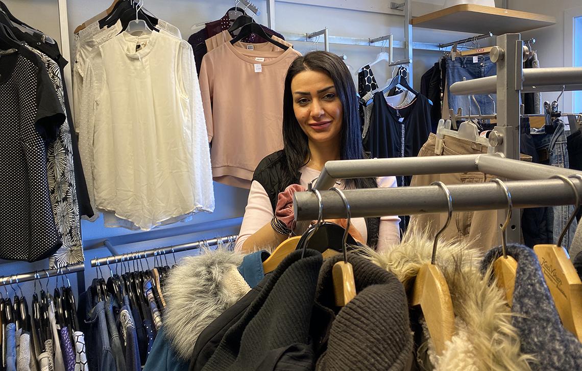dame med klær i bruktbutikk