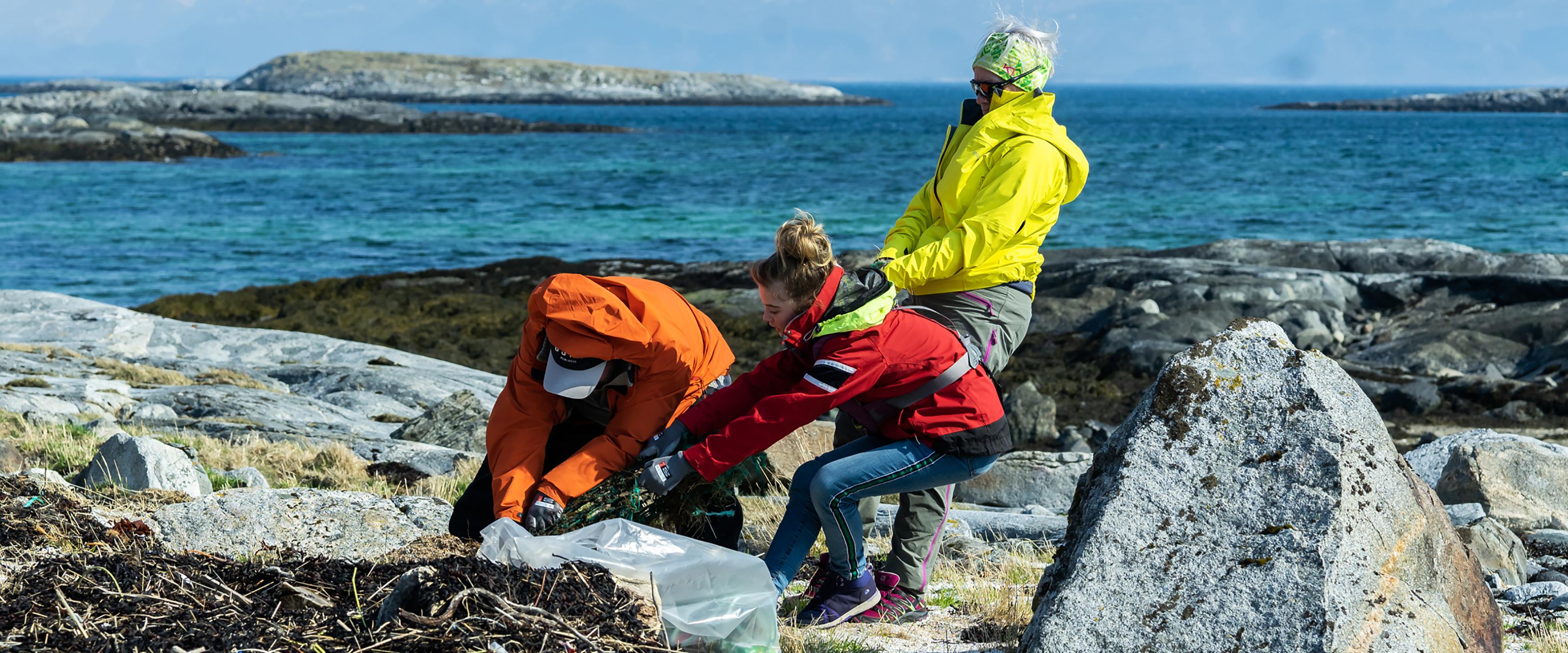 Personer som rydder avfall i strandsonen