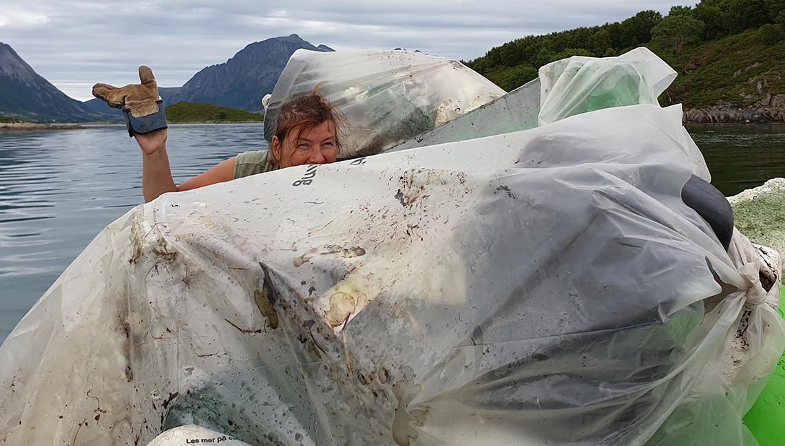 Dame i båt med marint avfall