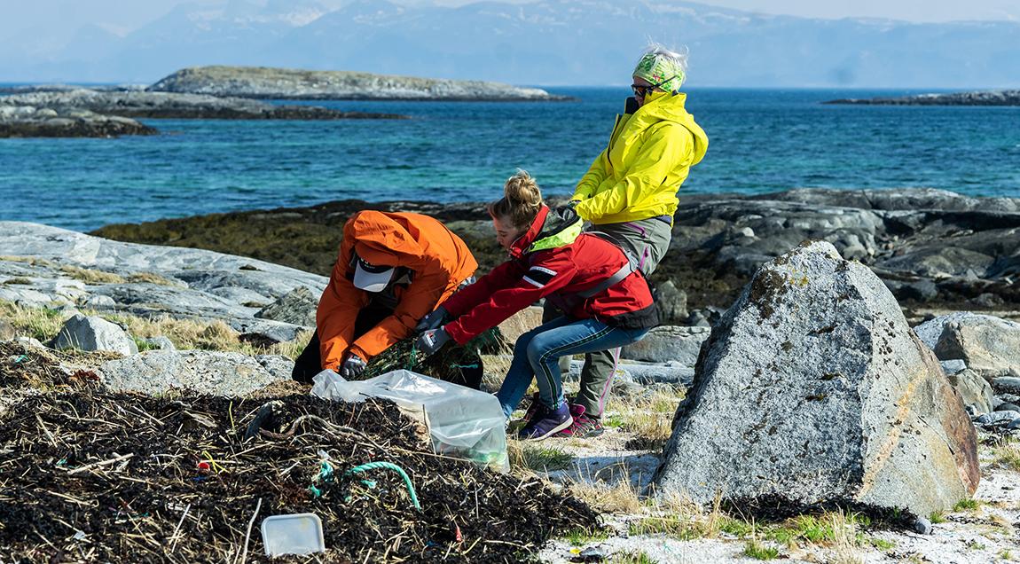 Tre personer rydder marint avfall