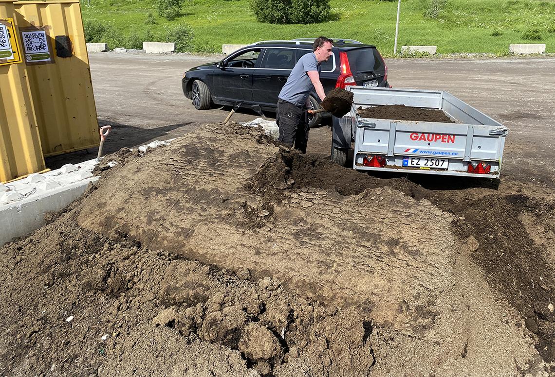 Man måker jord på biltilhenger