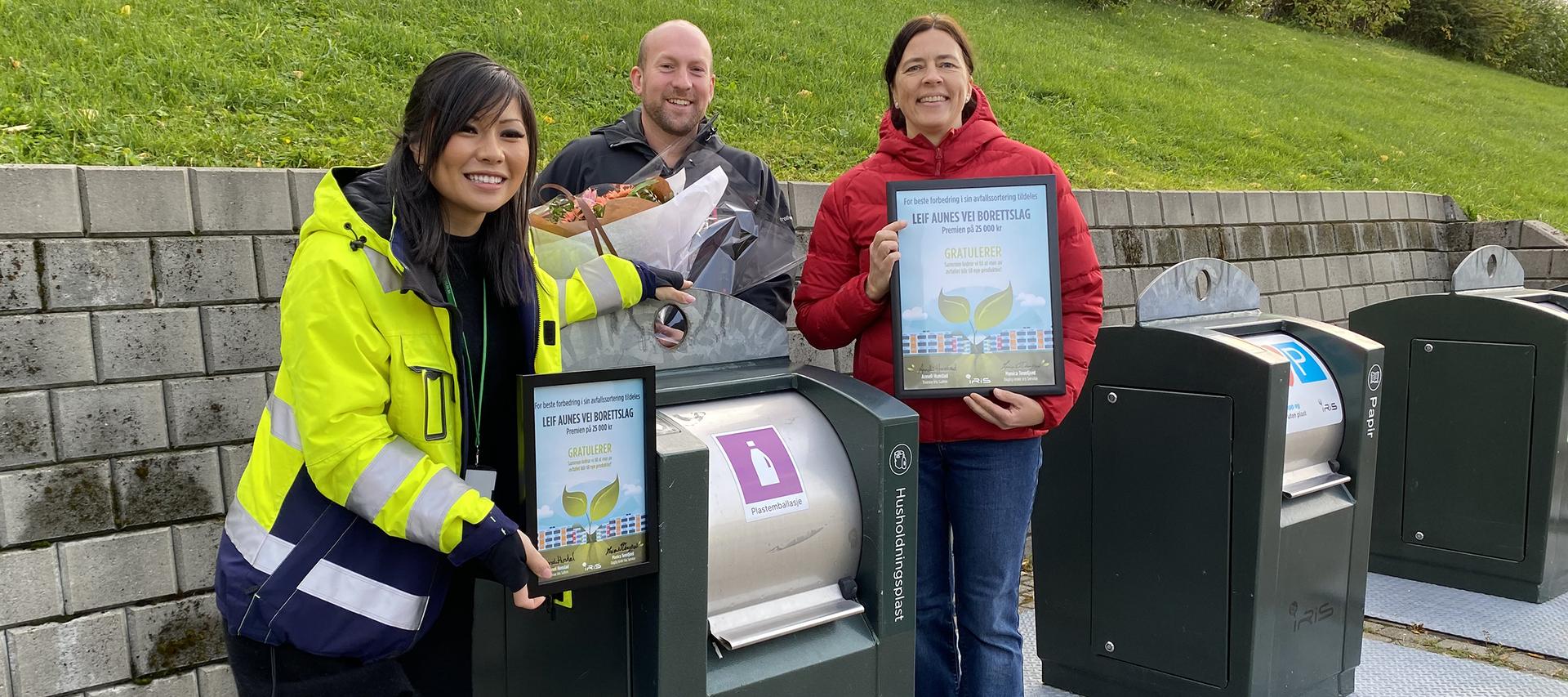 Tre personer foran avfallsanlegg