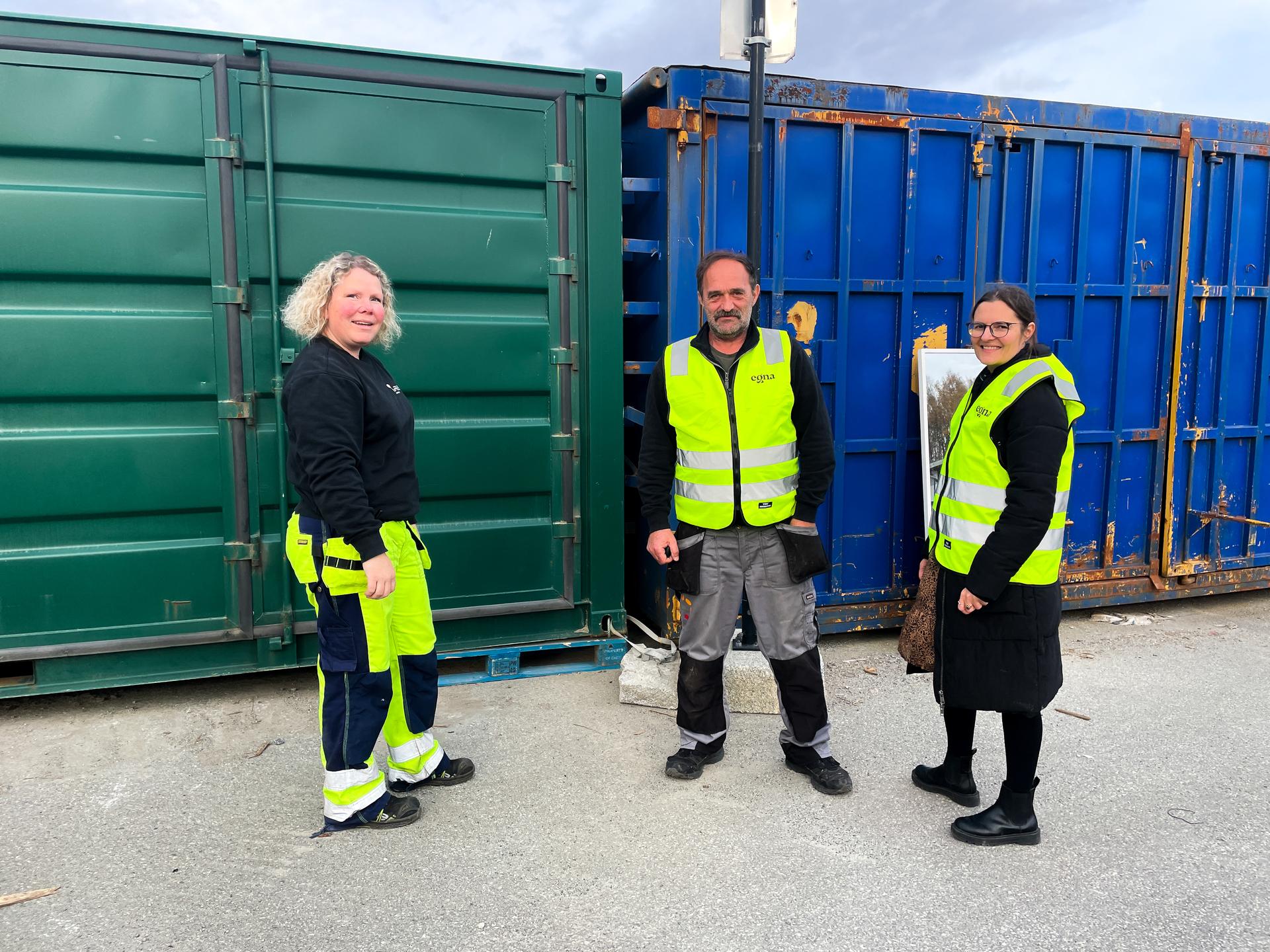 Tre mennesker utenfor en container